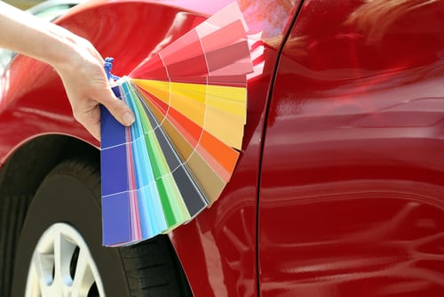 hand-with-paint-samples-choosing-color-for-painting-car