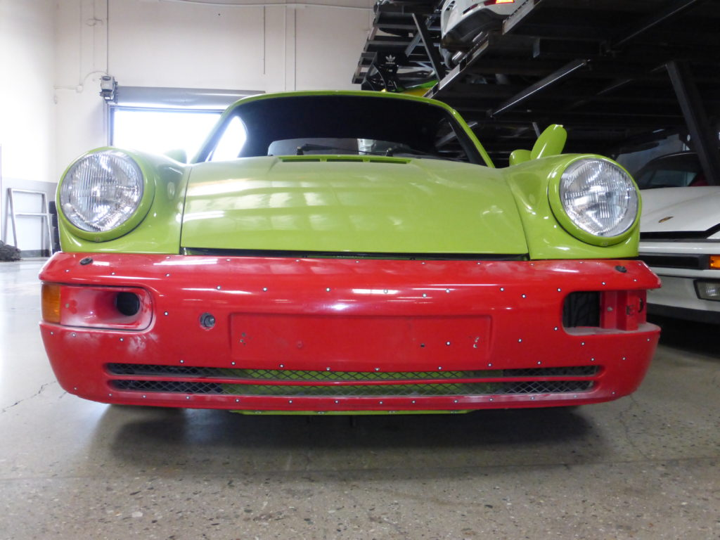 A 1993 Porsche® 964 with a customized front bumper and LED dash headlights.